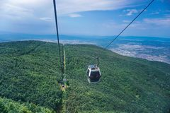 Cable cars going up in to the mountain, green hills stock image