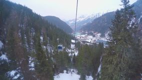 Cable cars moving up and down cableway in mountains covered with snow, forest. Stock footage stock video