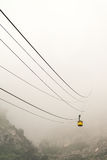 Cable cart on a foggy day. A yellow cable cart disappearing into the fog Stock Photography