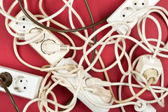 Cable chaos clutter from multiple electric wire extension cords. And multi-contact plugs on red background Stock Photos