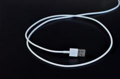 Cable connecteur blanc de données avec USB sur le fond noir photos stock