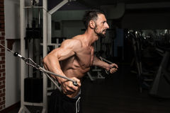Cable Crossover Chest Workout. Bodybuilder Is Working On His Chest With Cable Crossover In A Dark Gym stock photography