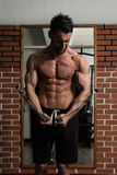 Cable Crossover Chest Workout. Bodybuilder Is Working On His Chest With Cable Crossover In A Dark Gym royalty free stock photography