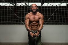 Cable Crossover Chest Workout. Mature Bodybuilder Is Working On His Chest With Cable Crossover In A Dark Gym stock photo