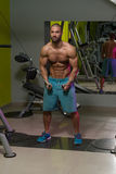 Cable Crossover Chest Workout. Young Bodybuilder Is Working On His Chest With Cable Crossover In A Dark Gym stock images