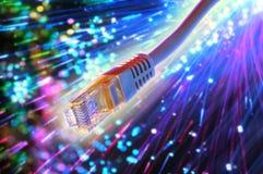 Cable de Ethernet con el fondo de la fibra óptica Fotografía de archivo