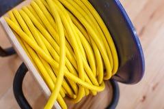 Cable de extensión eléctrico amarillo del alambre en el carrete Fotografía de archivo libre de regalías
