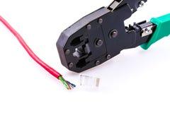 Cable de la red, conector RJ-45 y alicates que prensan Imagen de archivo