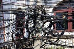 Cable de teléfono en un polo, edificio blanco foto de archivo