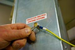 Cable de tierra del cableado que aprieta a la llave inglesa A imagen de archivo