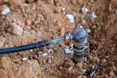 Cable de toma de tierra de cobre de la soldadura en la tierra Foto de archivo libre de regalías