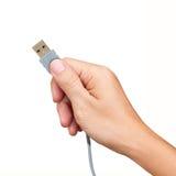Cable del USB de la explotación agrícola de la mano aislado en blanco Foto de archivo