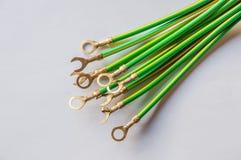 Cable eléctrico del verde amarillo con el estirón del cable aislado en blanco Foto de archivo
