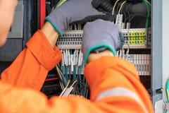 Cable eléctrico y del instrumento del técnico de cableado en el terminal y la caja de conexiones imagen de archivo