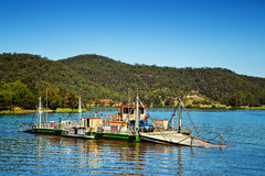 Cable ferry across a river in Australia. WISEMANS FERRY, AUSTRALIA - JANUARY 4,2015: Vehicles are carried across the Hawkesbury River by cable ferry. Open since Royalty Free Stock Images