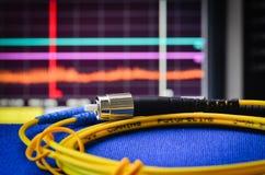 Cable fibroóptico con el analiser del espectro en el fondo Imagen de archivo