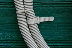 Electric cable in gray plastic insulation on a green wooden house wall. Cable in gray insulation on a wooden green wall Stock Photography