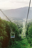 Cable hoist chair lift among woods view to top of mountain, summ Stock Photo
