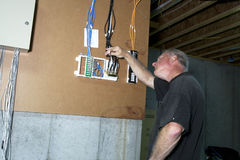 Cable Junction Box. Man connecting cable wires to punchboard in the basement of a house Stock Photo