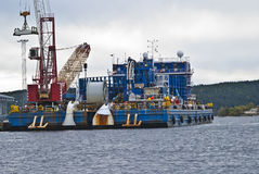 Cable-laying vessel. Large cable-laying vessels moored to the quay at the port of Halden. The crane that lifts the container standing on the pier Stock Photo