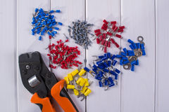 Cable lug in different colors and sizes, tools for crimping. royalty free stock images