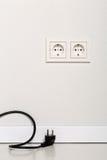 Cable negro del cable eléctrico desenchufado con el enchufe de pared europeo en wh Imagen de archivo libre de regalías
