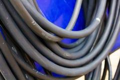 Cable negro grueso grande en fondo azul Fotografía de archivo