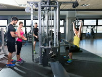 Cable pulley system gym workout fitness people. With personal trainer Royalty Free Stock Image