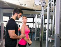 Cable pulley system personal trainer man and woman royalty free stock photos
