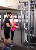 Cable pulley system personal trainer man and woman Stock Photo