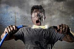 Cable que se une a del hombre inexperimentado que sufre accidente eléctrico con la expresión quemada sucia del choque de la cara Foto de archivo libre de regalías
