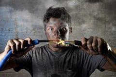Cable que se une a del hombre inexperimentado que sufre accidente eléctrico con la expresión quemada sucia del choque de la cara Imagenes de archivo