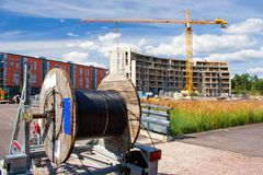 Cable reel in the construction site. A reel of heavy coaxial cable used for cable-TV underground construction, and the construction site in the background Royalty Free Stock Photography