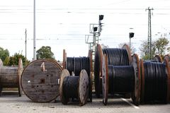 Cable reels. Large wooden cable pulleys with electric cables for rail transport royalty free stock image