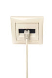 Cable with RJ-45 connector is connected to a wall outlet. Royalty Free Stock Photo