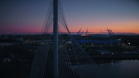 Cable stayed car bridge highway nearly modern sports stadium business skyscraper. Silhouette cable stayed bridge for car traffic on highway nearly modern sports stock video