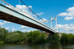 Cable-stayed footbridge over small river Royalty Free Stock Images