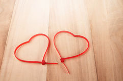 Cable ties heart shape on wood background , holiday abstract bac. Kground stock images