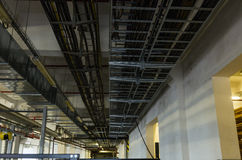 Cable trays and pipes in industrial building Stock Image