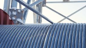 Cable uncoils from bobbin at electrical station. Closeup metal cable uncoils from special bobbin at electrical transmission substation on winter day stock video