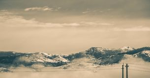 Cable Wires in Front of Snow Covered Mountains stock photos