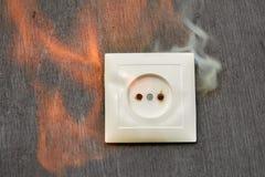 Cableado defectuoso, enchufe de pared del plástico del fuego foto de archivo libre de regalías
