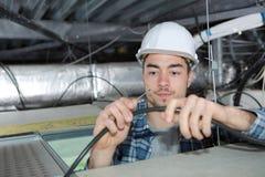 Cableado hermoso joven del electricista dentro del techo fotos de archivo