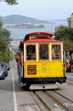 Cablecar with Alcatzar - San Francisco. The famous cablecar on top of a San Francisco Hill, with Alcatraz in the background Stock Photos