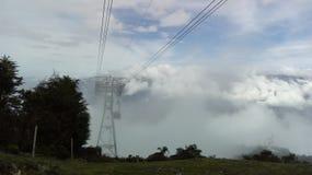 Cablecarril entre la neblina foto de archivo