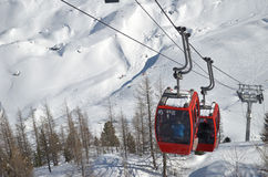 Cablecars moving up snow covered mountain Stock Images