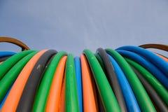 Cables anaranjados, azules, verdes de la telecomunicación Foto de archivo