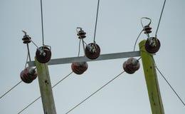 Cables de alto voltaje y aisladores de la corriente eléctrica vistos en polos de madera Imágenes de archivo libres de regalías