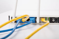 Cables de Ethernet amarillos y azules en router inalámbrico Imagen de archivo libre de regalías