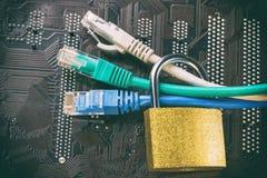 Cables de Ethernet de la red en candado en la placa madre del ordenador Concepto de la seguridad de información de la privacidad  Imagenes de archivo